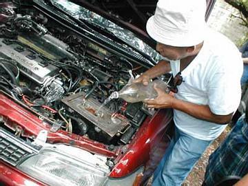 Daniel echándole agua como combustible a su coche de motor de hidrógeno