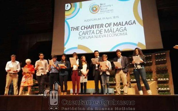 """Niños y adultos leen en grupo la """"Carta de Málaga"""", documento de referencia de la Nueva Economía."""