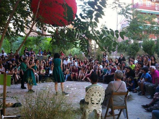 Los vecinos disfrutando de una obra de teatro en la plaza.
