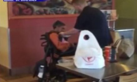 Joven empleado de una cadena de comida rápida le da de comer a una mujer discapacitada