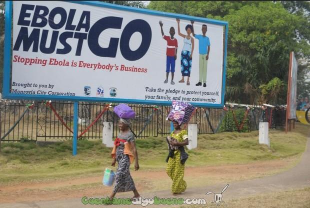 """Dos mujeres caminan delante de un cartel que dice """"El Ébola debe marcharse. Detener el Ébola es un asunto de todos"""" en Monrovia, Liberia. Foto: UNMEER."""