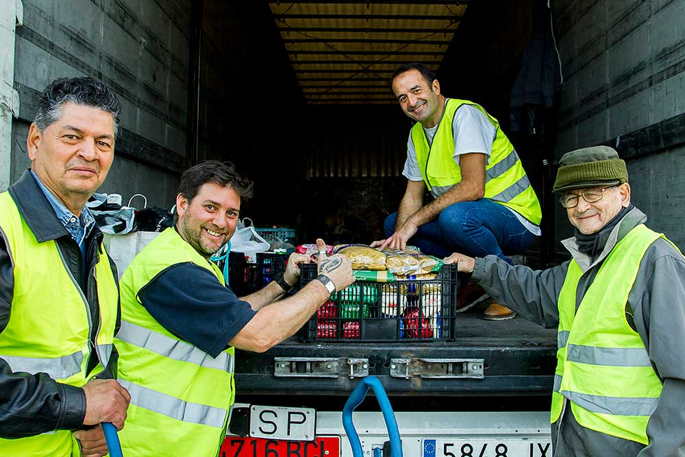 Voluntario cargando los alimentos donados por los asistentes para ser entregados a familias necesitadas