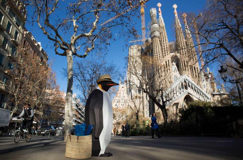 Un pingüino geométrico marcha simbólicamente a los pies de la Sagrada Familia de Barcelona