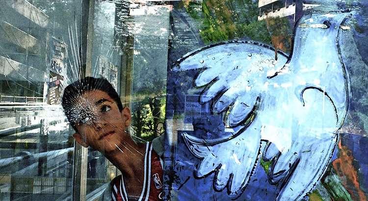 Un niño de Escuelas de la Paz de Europa, unto a un dibujo de una paloma de la paz